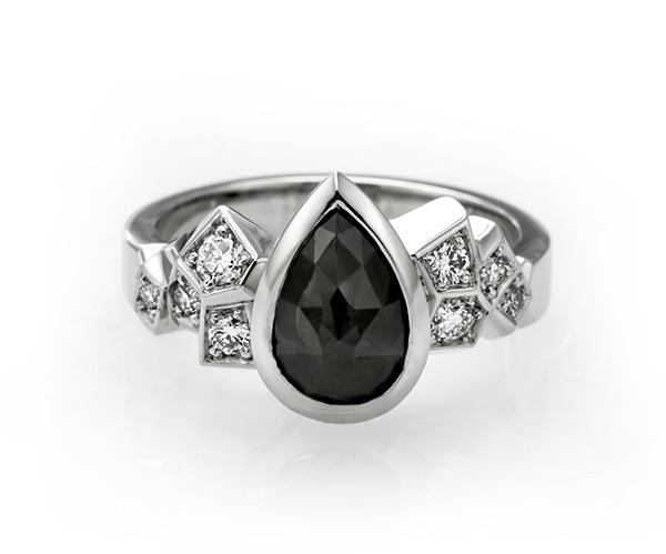 Kruunu-sormukseen on yhdistetty iso pisaran muotoinen musta timantti.